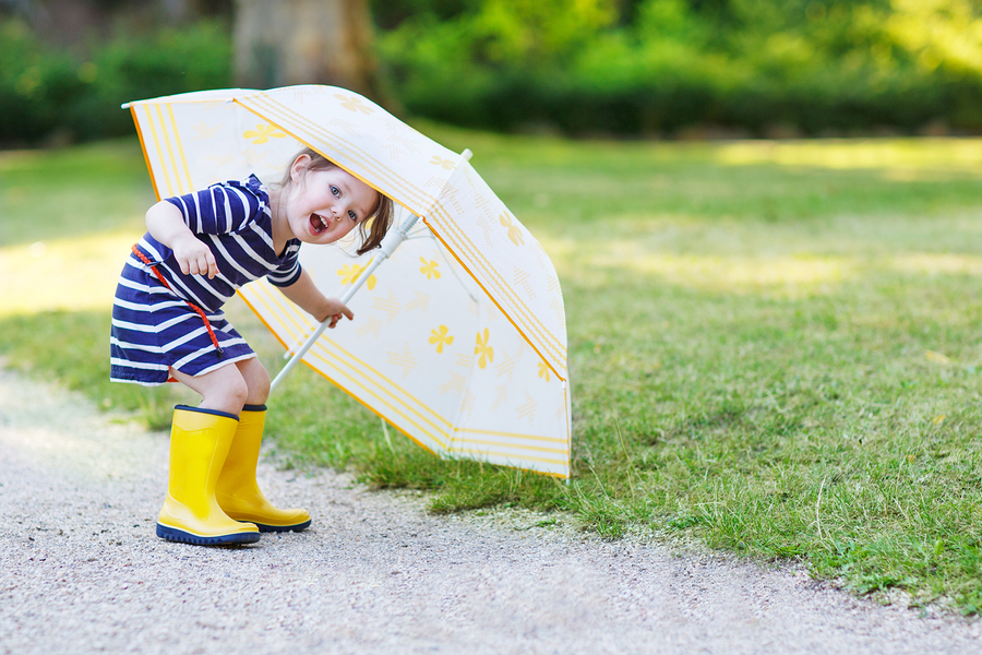 Adorable little toddler girl having fun with umbrella in yellow rain boots and umbrella in summer park.